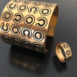 Coco Chanel logo gold cuff bracelet and ring set.